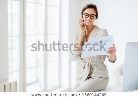 Attractive businesswoman reads papers or business documents, has telephone talk with business partne Stock photo © vkstudio