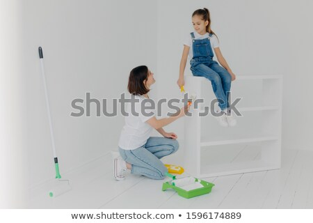 Pleased brunette mother looks at child, paint furniture in modern apartment, poses in spacious empty Stock photo © vkstudio