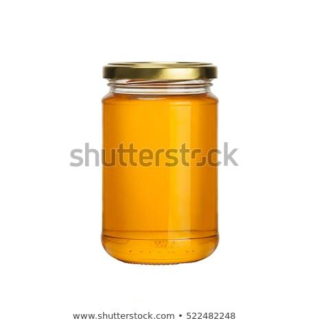 Miele jar a nido d'ape primo piano liquido giallo Foto d'archivio © FOKA
