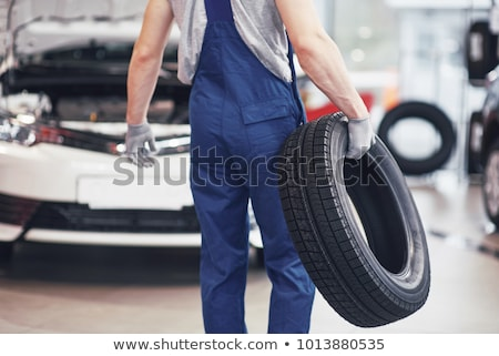 Mechanic changing car tyre in garage Stock photo © roboriginal