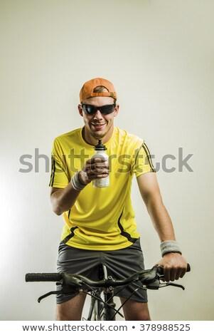 Mountain biker drinking water in studio Stock photo © ivonnewierink