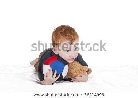 Boy with ball and teddy laying down Stock photo © sdenness