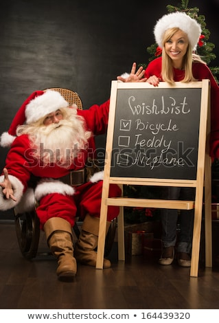 Santa Claus with his helper standing near chalkboard with wishli Stock photo © HASLOO