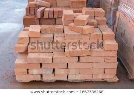Red clay bricks stacked on pallets Stock photo © juniart