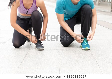 Man and woman tying shoelaces Stock photo © HASLOO