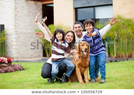 Smiling siblings petting their golden retriever Stock photo © wavebreak_media