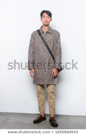 handsome young business man wearing a brown leather coat stock photo © feedough