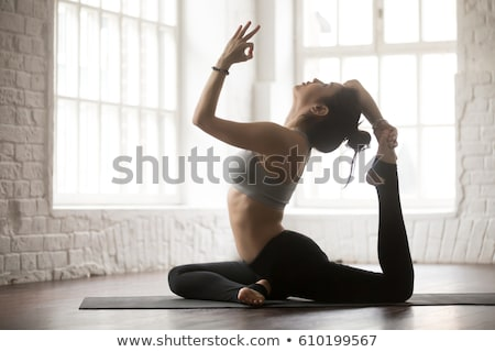 Stock photo: Woman doing yoga exercises in fitness gym