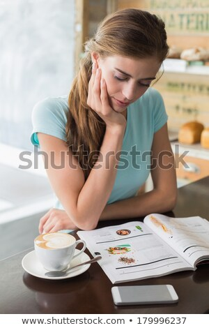 woman reading magazine in a bar stock photo © deyangeorgiev