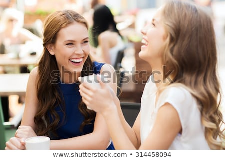 two smiling women drinking coffee and talking in outdoor cafe stock photo © deandrobot