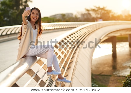 Smiling woman sitting on railings Stock photo © dash