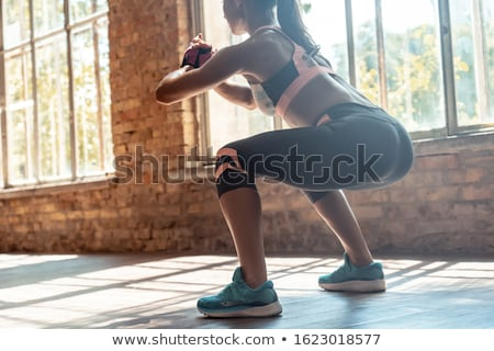 Concentrated strong sports lady standing in gym Stock photo © deandrobot