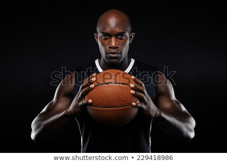 Сток-фото: Young Athletic Man Basketball Player Standing With Ball On Black