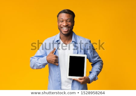 smiling african man showing blank tablet computer screen stock photo © deandrobot