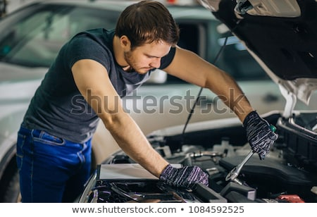 Mechanic working under car smiling Stock photo © monkey_business