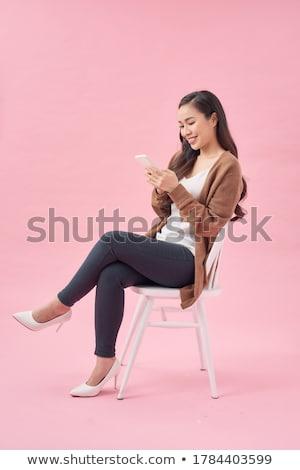 Atraente mulher jovem sessão cadeira celular branco Foto stock © iofoto