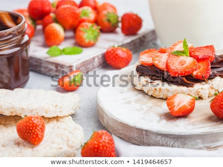 healthy organic rice cakes with chocolate butter and fresh strawberries on wooden board and glass of stock photo © denismart