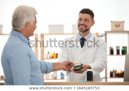 apothecary selling drug to senior man at pharmacy Stock photo © dolgachov
