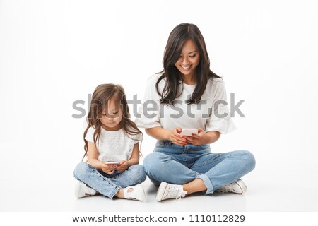 happy young asian beautiful attractive woman posing isolated indoors using mobile phone stock photo © deandrobot