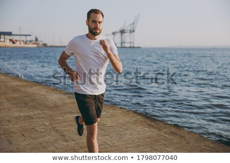 Image of muscular sporty man 20s in shorts and t-shirt running a Stock photo © deandrobot