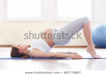 a sporty pregnant woman exercising holding belly stock photo © lopolo
