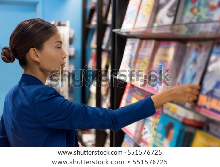 Businesswoman reading magazines at newsstand store of airport or train station. Asian woman shopping Stock photo © Maridav
