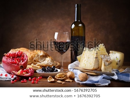 pomegranate, walnuts and glass of wine on a wooden background Stock photo © zoryanchik