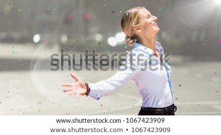 Business woman arms outstretched against blurry street with flare and confetti Stock photo © wavebreak_media