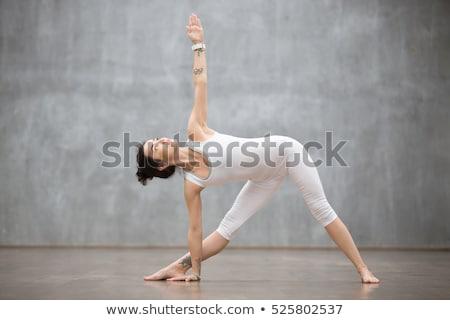 Woman in triangle Yoga posture (Trikonasana) Stock photo © lichtmeister