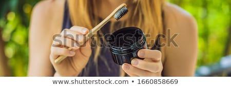 Mulher jovem escove dentes carvão vegetal pó branqueamento Foto stock © galitskaya