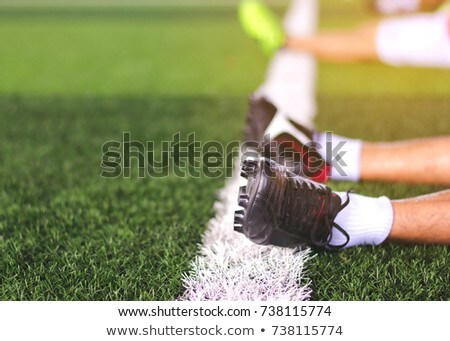 soccer player relaxing on grass stock photo © is2
