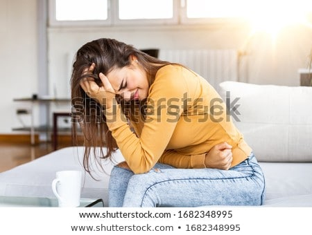 Woman Suffering From Stomachache On Sofa Stock photo © AndreyPopov