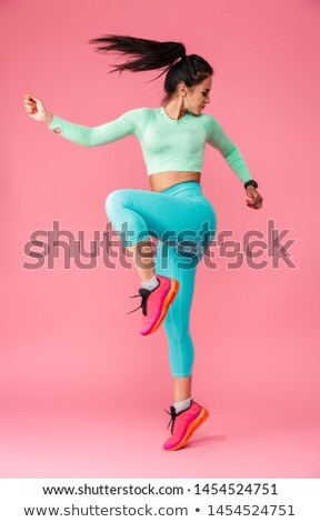 Picture of young beautiful fitness girl makes sport exercises with sea coast on background Stock photo © ElenaBatkova