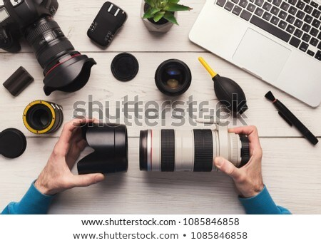 Professional technician repairs disassembled parts of camera, holds tweezers, works in service cente Stock photo © vkstudio