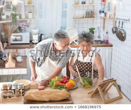 loving couple standing in the kitchen with digital tablet stock photo © boggy