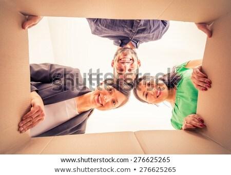 Group of friends unpacking the cardboard box Stock photo © Kzenon