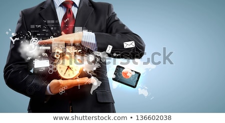 business man holding a clock against background with clocks stock photo © wavebreak_media