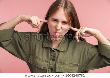 Photo of displeased woman plugging her ears and sticking out her tongue Stock photo © deandrobot