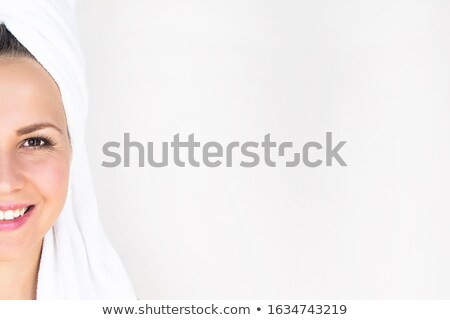 Radiant caucasian woman with a towel on her body smiling at the camera against a white background Stock photo © wavebreak_media