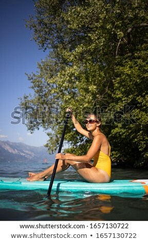 Pretty, young woman paddle boarding on a lovely lake  Stock photo © lightpoet