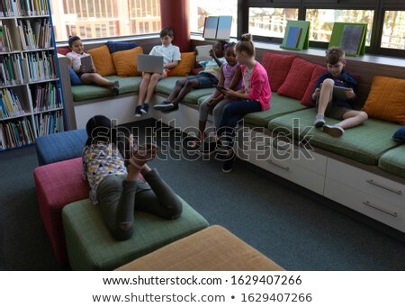 Front view of group of schoolkids studying while sitting on the couch in school library Stock photo © wavebreak_media