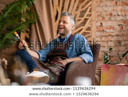 Cheerful artist in workwear laughing at detail of painting in studio Stock photo © pressmaster