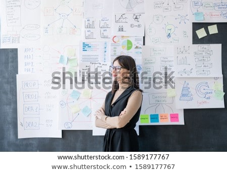 Young economist standing by blackboard with flow charts and diagrams on papers Stock photo © pressmaster