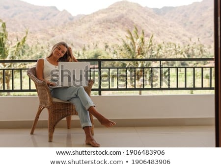 Young woman is working on a laptop on her balcony overlooking the skyscrapers. Freelancer, remote wo Photo stock © galitskaya