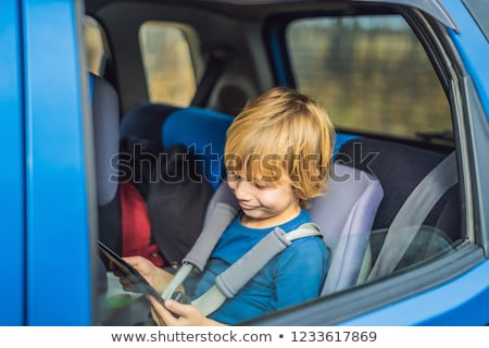 Little boy traveling on backseat of a car using touch pad to entertain himself during the trip Stock photo © galitskaya