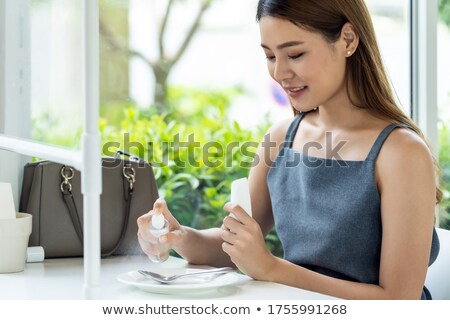 Asian woman spraying alcohol on restaurant dishware Stock photo © vichie81