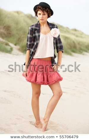 Fashionably Dressed Attractive Young Woman Standing Amongst Sand Stock photo © monkey_business