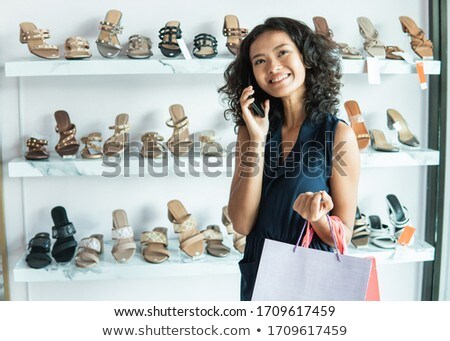 young woman calling on smartphone at shoe store stock photo © dolgachov