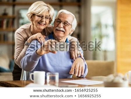 image of caucasian couple using mobile phone and taking selfie p stock photo © deandrobot