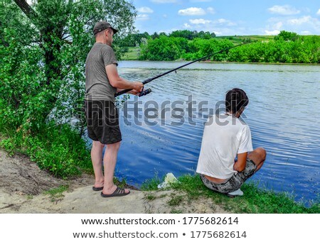 young friends enjoying fishing on sunny day at a calm lake stock photo © boggy